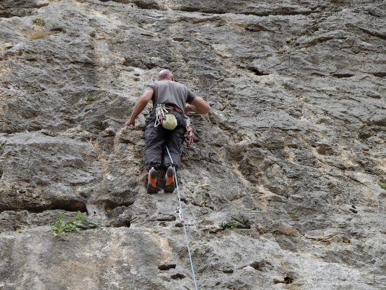 Climber has the rope behind his leg and risks falling upside down